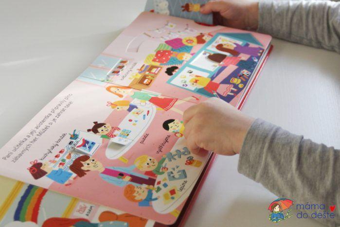 Ať žije školka - děti jsou v herně. Tabule se dá otáčet a mění se na ní obrázky, holčička stříhá papír, trouba má odklápěcí dvířka.
