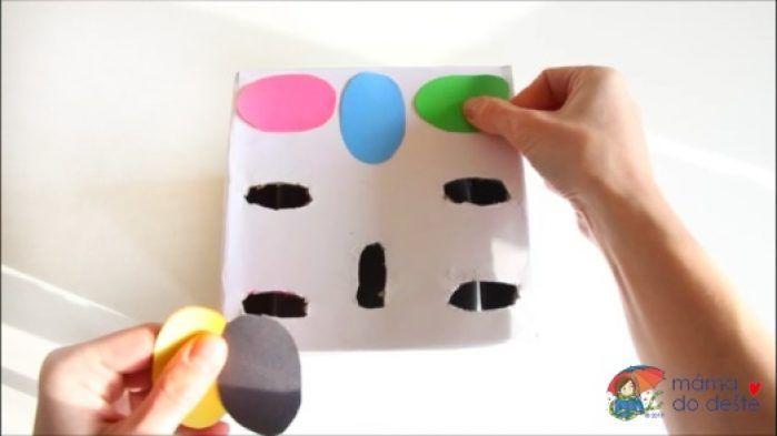 Do krabice jsem vyřezala osm otvorů a následně jsem je polepila barevným papírem.